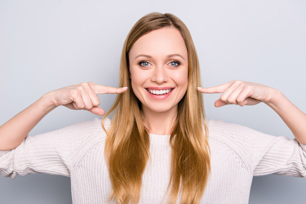 Smiling woman pointing at her perfect teeth